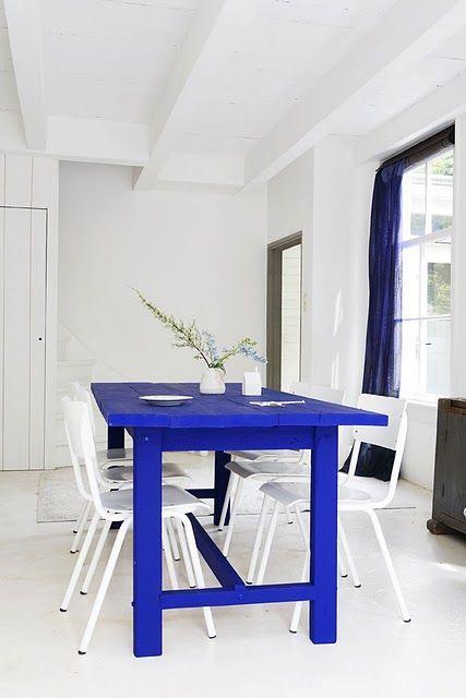 Mesa pintada de azul cobalto combinada com cadeiras brancas, ambiente branco, a esa se destaca. Estilo de decoração inspirada no Mediterrâneo