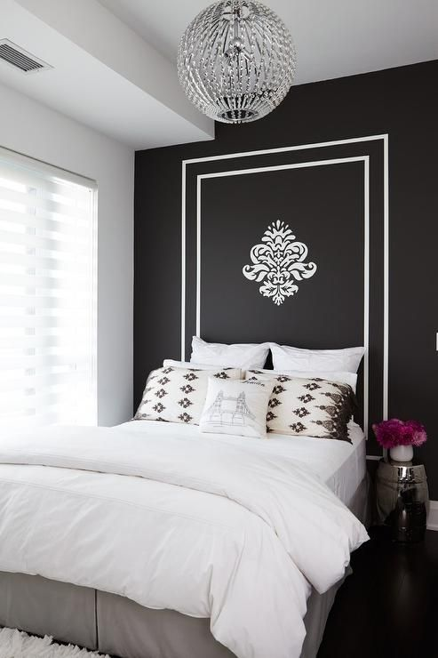 Gorgeous bedroom features a black and white painted headboard with fleur de lis on full bed dressed in white bedding and gray pleated bedskirt next to a silver garden stool illuminated by a clear beaded chandelier.