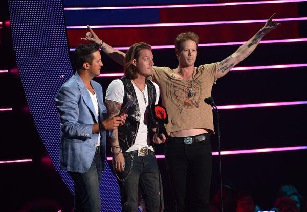 "Two-time winners Florida Georgia Line accept the buckle for ""This Is How We Roll"" with pal Luke Bryan at the 2014 CMT Music Awards."
