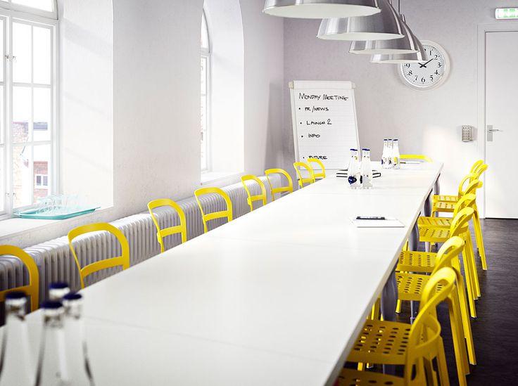 Sala riunioni con un lungo tavolo bianco composto da tanti tavoli più piccoli, e sedie giallo canarino