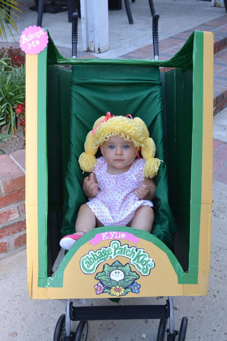 Infant girl DIY cabbage patch kid Halloween costume. Made from cardboard box, paint, and zip ties. The baby wig is DIY as well, made with yarn.
