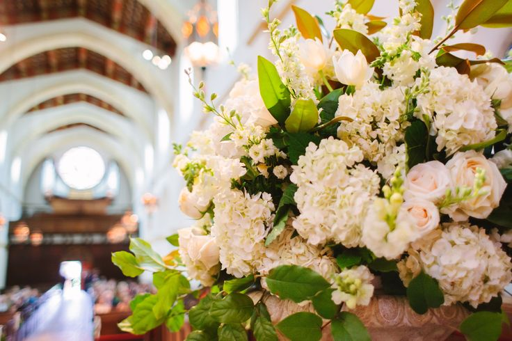 detail of large structured altar urns of white hydrangea, white roses, champagne roses, white larkspur, white french tulips, white snapdragons and lemon leaf.