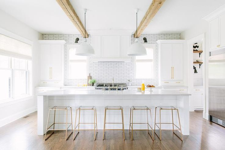 Stunning white kitchen boasts five brass and Lucite counter stools sat in front of a large stunning white shiplap island topped with white quartz countertops fitted with a sink and polished nickel deck mount faucet lit by two white modern pendants hung from a wood beam ceiling.