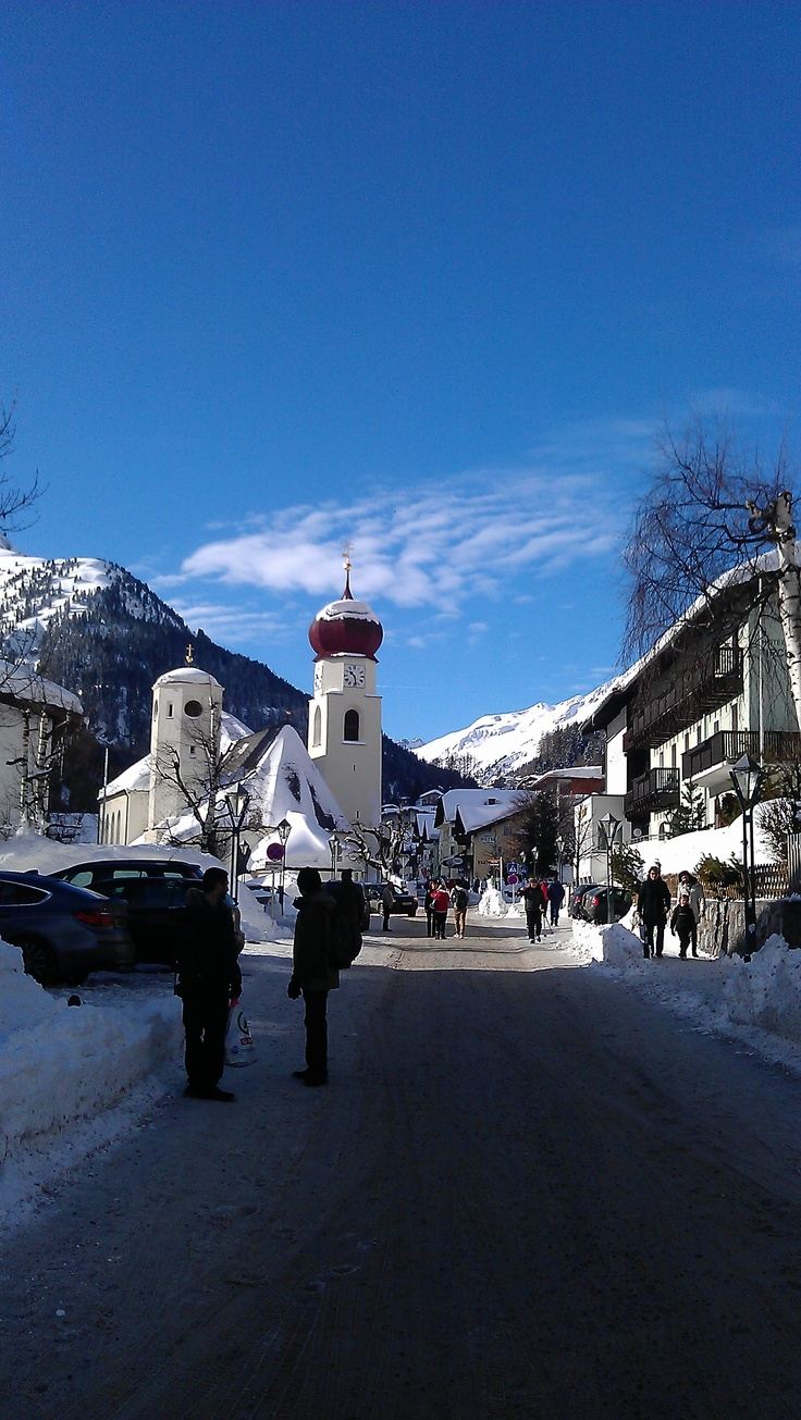 Main street in St Anton - in the middle of the village  with the cute Onion tower church - the snow is still plenty, as one can see, so it's good to go skiing - let's hit the slopes on the shadowy side of the valley to the left, cause the snow is better there in springtime around Easter...