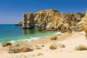 Guia de Praias do Algarve | Popular Villas - A praia da Coelha encontra-se acessível por um caminho que serpenteia por entre campos agrícolas, onde poderá apreciar um pouco da paisagem tradicional do Algarve, rica em oliveiras e alfarrobeiras centenárias. Uma vez na praia, os visitantes irão descobrir uma pequena enseada, protegida por imponentes falésias. Coordenadas de localização: GPS N 37º 4' 23.05'', W -8º 17' 15.35''