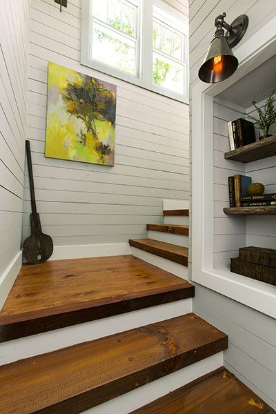 A wall in the stairwell with 3-inch-thick stair treads reclaims dead space with a niche fitted with three reclaimed-wood shelves and a sconce to light the display. Photo: Deborah Whitlaw Llewellyn