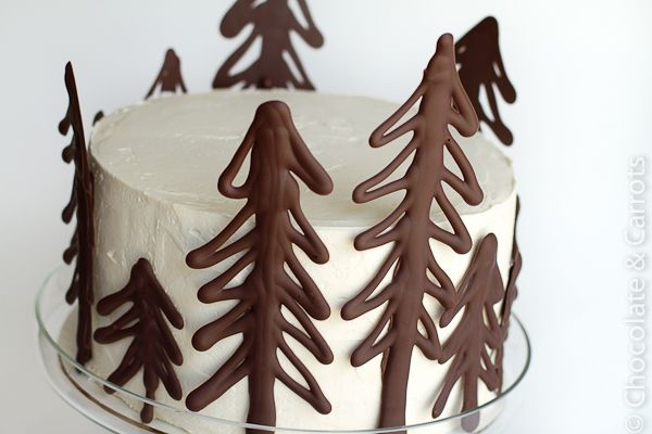 simple white buttercream cake with chocolate trees on side