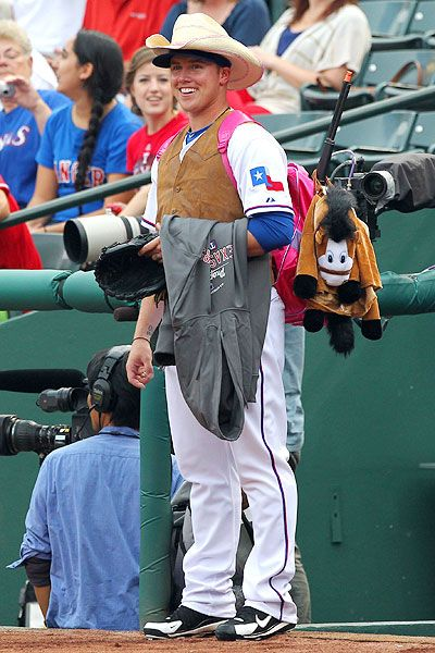 Robbie Ross, pitcher - hazing from the Texas Rangers team.  Note the pink Dora the Explorer backpack that transports the team's snacks for each game.