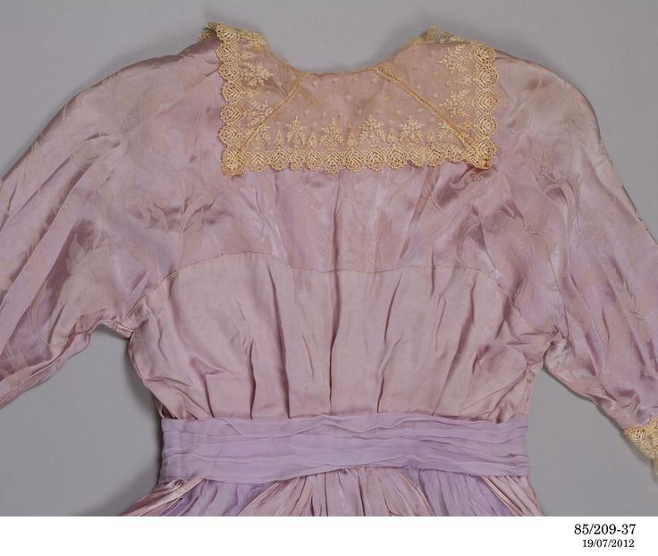 Day dress, silk / satin, designer and maker unknown, c. 1913 A full length day dress made in lilac coloured satin with a boned back fastening and a high waist. The dress has long sleeves with internal sweat pads under each arm and an embroidered cream net from elbow to wrist, and a cream embroidere...