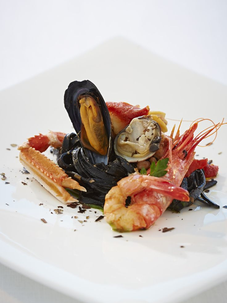 Linguine pasta made with black cuttlefish sauce and served with seafood