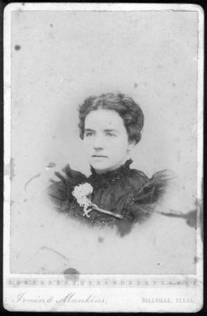 Photograph of Mrs. J. G. Wessendorff as a young woman. Wessendorff is wearing a dark dress with ruffled netting at the shoulders. Beadwork trim at neckline and around bodice. She has a flower on her right shoulder with the stem extending across her upper chest. Her dark hair is parted in the center. Photograph is mounted on a cardboard substrate with gold design that separates photo from photographer's name in gold: Irwin & Mankins, Bellville, Texas.    Creator(s):Irwin and Mankins