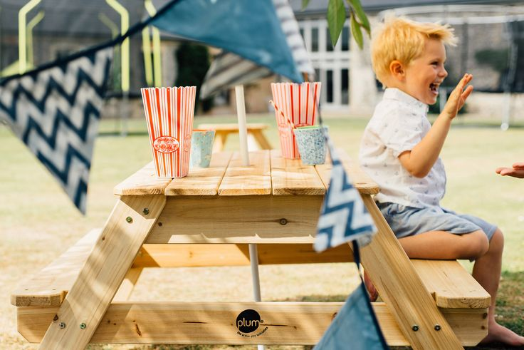PLUM PICNIC TABLE WITH UMBRELLA  Plum's Wooden Picnic Table with Parasol is the bench of choice for children dining al fresco!  The wooden picnic table includes a colourful parasol to keep little ones shaded and cool in the sun.   Suitable for ages 18 months and over.