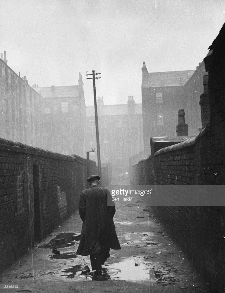 A man walking through a backstreet in the rundown Gorbals area of Glasgow The Gorbals tenements...