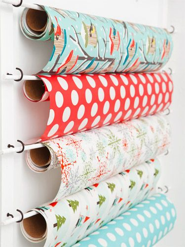 DIY:  Cup hooks and dowels holding wrapping paper... easy!  This would be a great way to store foil, saran wrap, etc. in the kitchen.