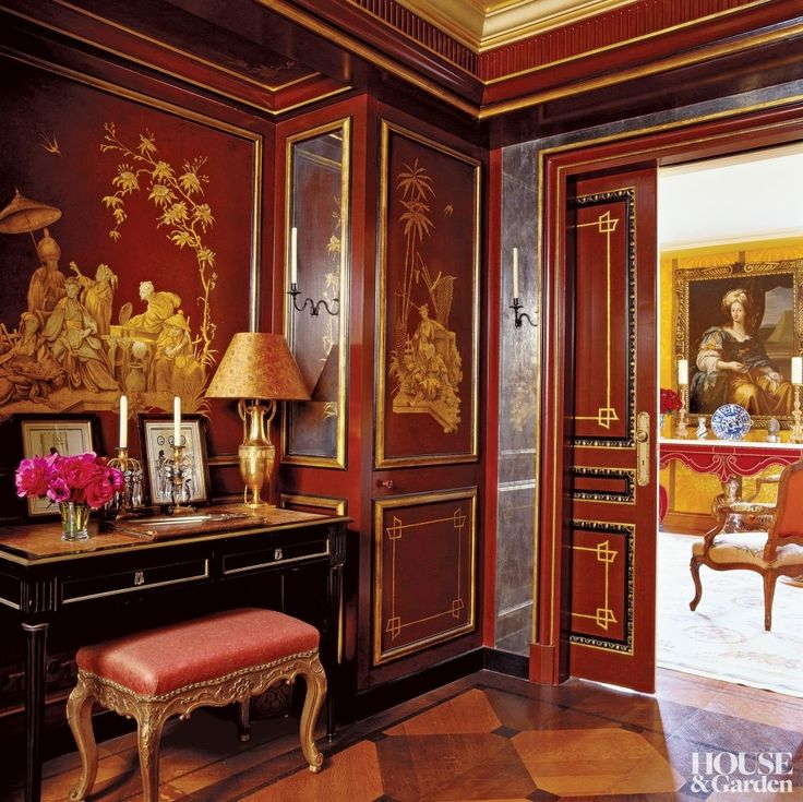 Exotic Bedroom by Alidad in Paris, France In the Chinese boudoir of a Parisian pied- -terre, an antique Empire-style gilded lamp and English Regency candlesticks sit atop an early-19th-century French desk. Lacquered wall panels conceal storage cupboards, making the space practical and decorative.