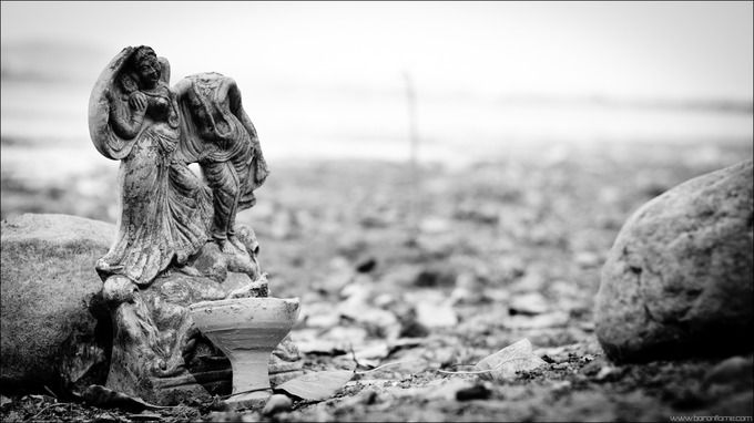 A broken immersed idol on the dried lake bed