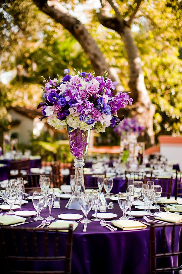 Purple tablecloth with purple, lavendar, ivory, and dark blue floral centerpiece - clear glasses and dishes.