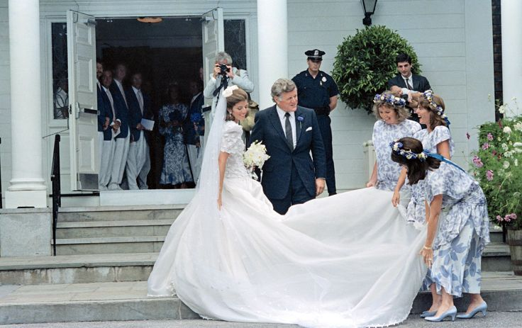 Caroline Kennedy, in a dress scattered with shamrocks and designed for her by Carolina Herrera, with her uncle Senator Ted Kennedy, who gave her away to Edwin Schlossberg, outside Our Lady of Victory Church in Centerville, Massachusetts, in 1986.    Photo: Bettmann/Corbis