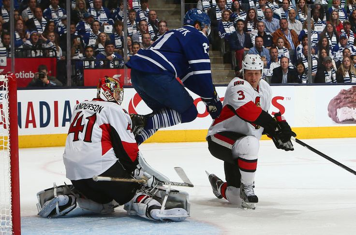 TORONTO, ON - OCTOBER 5: James van Riemsdyk #21 of the Toronto Maple Leafs dodges a shot on goal against Craig Anderson #41 and Marc Methot #3 of the Ottawa Senators during the home opener at the Air Canada Centre October 5, 2013 in Toronto, Ontario, Canada.