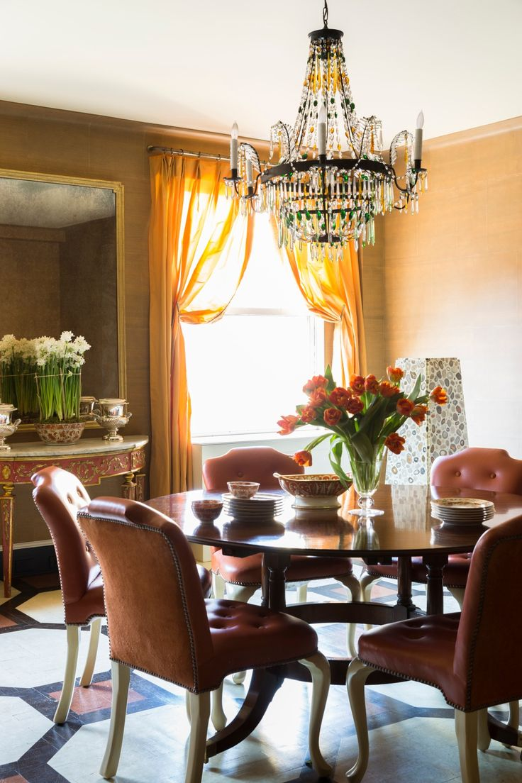 In the dining room, above a vintage Regency-style table by Jonathan Burden, sits a 19th-century Austrian chandelier opposite artwork by Janaina Tschäpe on one wall, and an oversized antiqued mirror on the other.