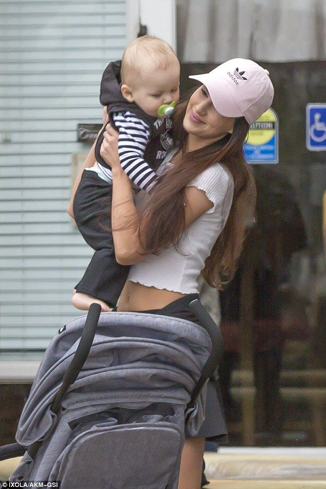 Loving mother: Her long brunette tresses cascaded from underneath her cap, and she sported a slick of pink lipstick