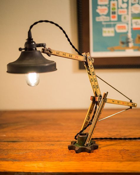 Unruly is a killer desk lamp art piece! It starts as a vintage Lufkin folding ruler out of my grandfathers shop. I probably used this as a kid building his lake house. The base is a vintage John Deere gear and the brass (nice patina!) supports and spacers are all hand made. The end supports (that the brass connects to) are steel and hand made. They are oil hardened and blackened for a natural protection against oxidation. This is a GREAT gift for the carpenter or woodworker who has…