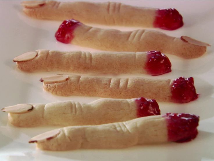 Witch Finger Cookies : Giada De Laurentiis transforms classic ladyfinger cookies into spooky witch fingers by adding almond fingernails and dipping the blunt ends in jam.