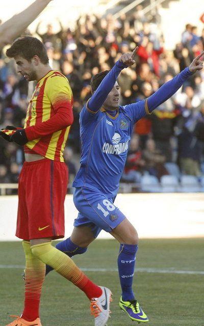 El defensa del Getafe Sergio Escudero celebra el primer gol de su equipo junto al defensa del Barcelona Gerard Piqué