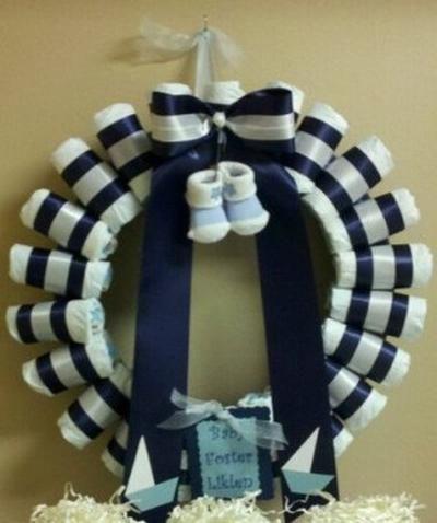 mooie baby boy geboorte krans: blauwe linten,etiket, strik en sokjes. De krans zelf zijn luiers, je kan ook eventueel ook rompertjes, slabbertjes of sokjes doen