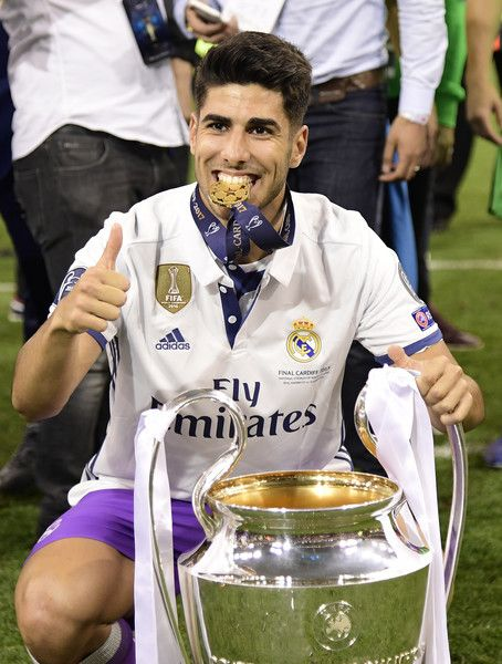 Real Madrid's Spanish midfielder Marco Asensio poses with the trophy after Real Madrid won the UEFA Champions League final football match between Juventus and Real Madrid at The Principality Stadium in Cardiff, south Wales, on June 3, 2017. / AFP PHOTO / JAVIER SORIANO