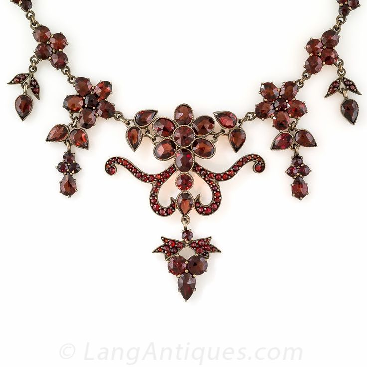 Bohemian Garnet Necklace. From early-twentieth century Czechoslovakia (aka Bohemia), comes this extravagant fringe necklace, aglow with dusky faceted almandine garnets. The necklace is designed with a fanciful flower and scroll motif centerpiece accompanied left and right by graduated floral drops. A ravishing, romantic vintage adornment crafted, per usual in warmly patinated (formerly gilded) metal.