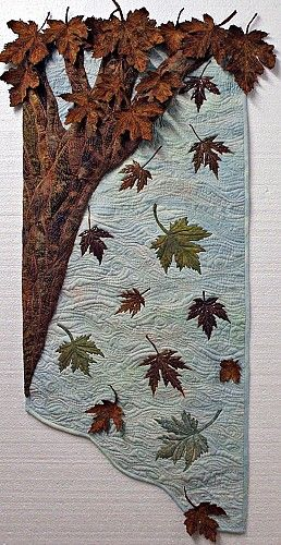 """Reality Show by Quilt Rat, Ontario, Canada All but 3 of the leaves on this quilt are actual maple leaves that had been preserved and then extensively thread painted, while others are under a layer of tulle. The background fabric is hand painted, the tree is 3D. The 3 """"fabric"""" leaves have text on them that speaks of my Canada. Original design"""