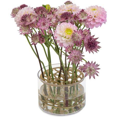 Äng vas från Klong, formgiver av Eva Schildt. En enkel glasvas med tillhörande metall-ställning som har ett vackert mönster och som fungerar som blomsterstöd. Det blir enkelt och fint att skapa arrangemang med snittblommor. Vasen är i klart glas och metallen i mässing.