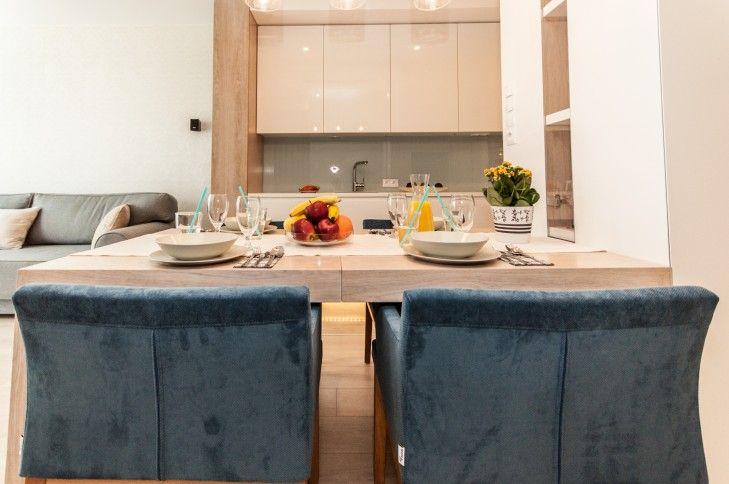 Projekt wnętrz pastelowej jadalni połączonej z kuchnią. Dużo bieli, jasne drewno i pastelowe szkło zostało ożywione mocniejszym akcentem kolorystycznym w postaci krzeseł.