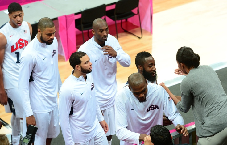 Michele Obama hugging US Men's basketball team after their first round win against France.  She IS a rock star.