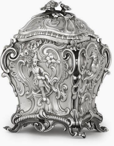 A George III sterling silver Chinoiserie-decorated tea caddy -  by John Langford and John Sebille, London, 1762 Of shaped rectangular cartouche form, each side finely chased with various figures in Chinese costume, on a cast and chased rocaille ground, with conforming cover and feet, total weight approximately 9oz troy. total height 5 1/4in (13.4cm); length 3 5/8in (9.2cm); depth 3in (7.6cm).