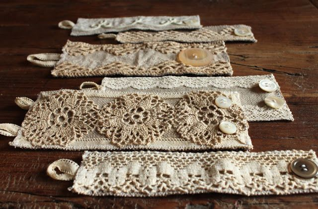 """cut out rectangles of heavy linen: the longest side should be about 0.75"""" wider than the circumference of your wrist. Pin on strips of lace, pieces of doilies. Don't be afraid to layer several things over one another. Once everything is pinned on, secure everything with tiny little stitches. Sew """"button loops"""" on one end, using a thinner ribbon, and mother of pearl buttons on the other end."""