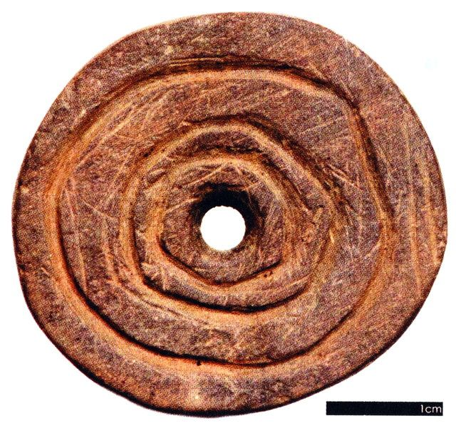 Bronze Age Spindle whorl - This decorated spindle whorl was discovered inside a Late Bronze Age house that was excavated by Bernice Molly at Killmelly, Co. Tipperary (Molloy 2009, 67). Used to make thread, spindle whorls played an important role in textile production. They consist of a perforated disc that was originally attached to a spindle stick. When the spindle was spun and then dropped with a wisp of wool attached the momentum of the spinning action was maintained by the whorl