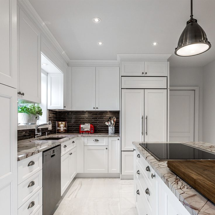 This beautiful transitional style kitchen wears white lacquer kitchen cabinets and a beautiful brown and white granite countertop that fits perfectly with the butcher block.  By : Quebec Cartier.