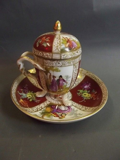 A C19th Meissen porcelain chocolate cup, cover and saucer, decorated with panels of flowers and romantic couples, cup is 4'' high (AF), saucer 6'' diameter: