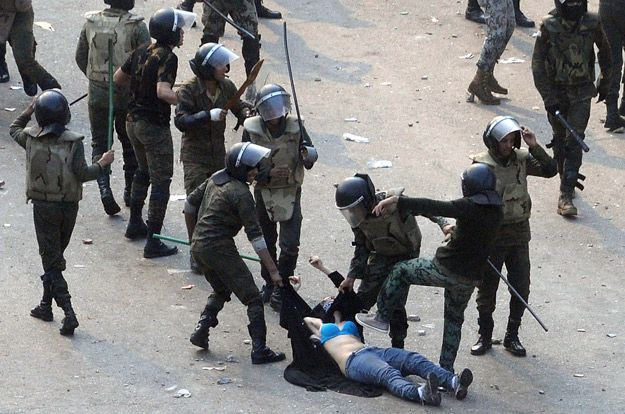 Egyptian army soldiers arrest a female protester, after ripping off her clothes, during clashes at Tahrir Square in Cairo Dec. 17, 2011