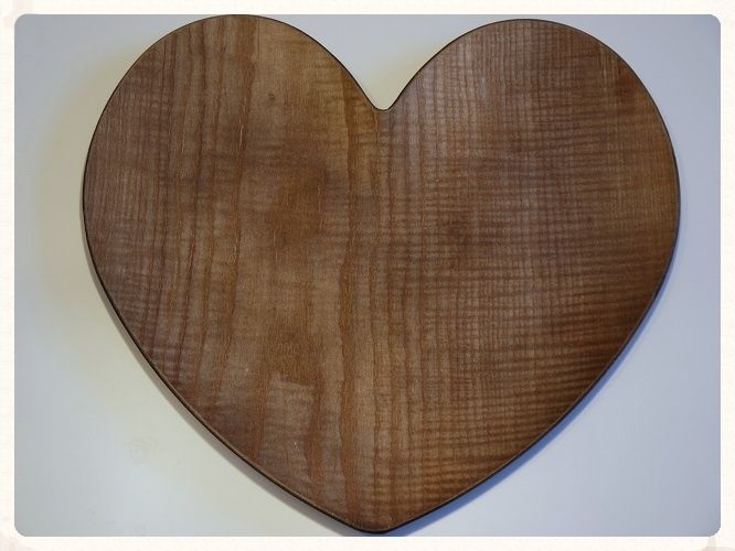 A large heart shaped brown wooden charger platter with plastic base which slightly curves up at the edges Ideal to use as part of a centrepiece and