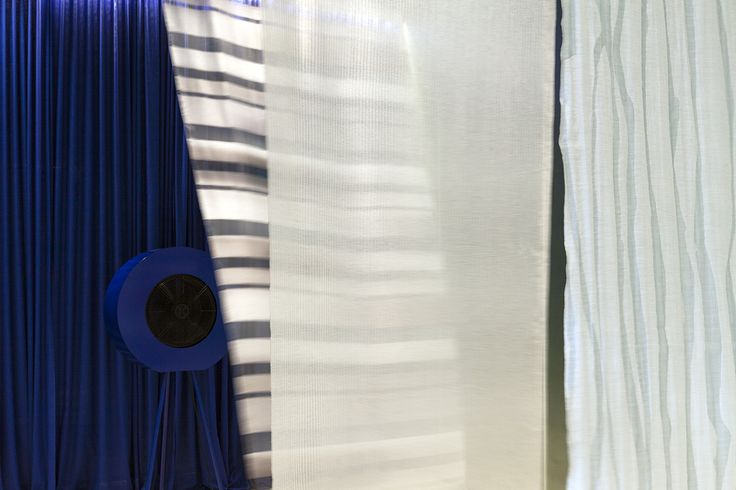 A textile installation in our Milan showroom by Studio Elisa Ossino. From the CONSTRUCTURE collection, an airy setting is created by semi-transparent curtains against an Yves Klein blue background. The fan placed at the back of the room generates an air wave that beautifully moves the light textiles.
