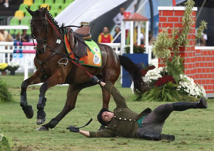 Justinas Kinderis of Lithuania falls during the show jumping round of Modern Pentathlon on Day 15 of the Rio Olympics
