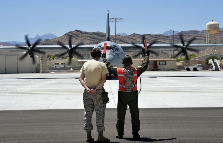 Tech.Sgt.Segric Hayes,right,of 818th Global Mobility Squadron,McGuire AFB,N.J.,marshals C-130J Super Hercules as prepares to take off from Creech AFB,Nev.,June 22,2014.Hayes and other 818th CRG Airmen,along with C-130H and C-130J models from various units,participated in Joint Forcible Entry,an exercise that helps Army and Air Force improve services cohesiveness and work together to properly execute large scale heavy equipment and troop movement.(USAF 1st Lt.Stephani Schafer)