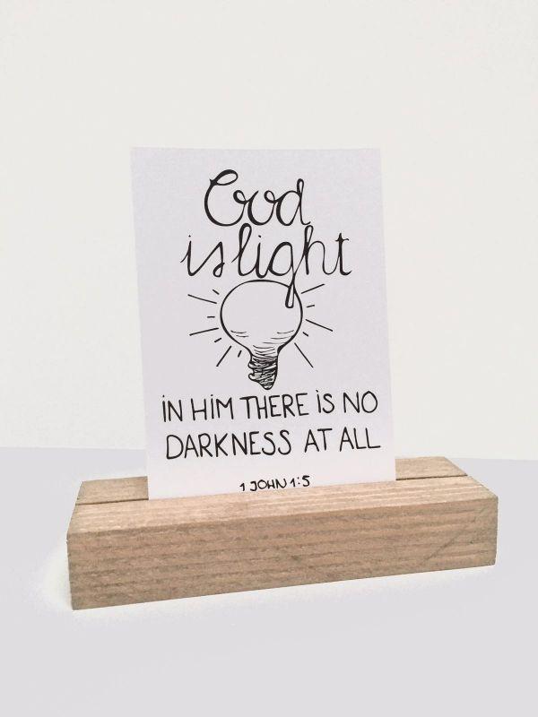 God is light (bible verse) bemoedigingskaart op een houten kaarthouder.