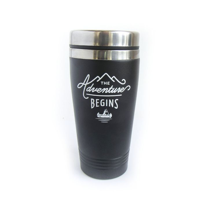 "This travel mug is black with white decaling and a silver lid. The decal features the expression ""The Adventure Begins"" as well as a mountain scene and a man canoeing. Look closely, the canoe is engra"