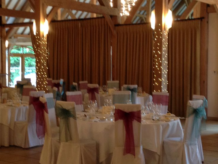 Chair covers with merlot & emerald green sashes ideal for an Autumn or Christmas wedding at Rivervale Barn styled by Fuschia.