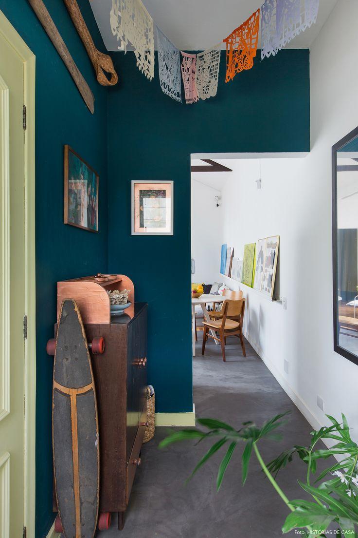 Hall de entrada de apartamento tem parede pintada de azul, porta amarela e móvel de madeira vintage.
