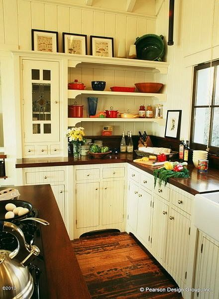Trim work on the shelves gives so much charm.  Love the beadboard cabinetry and dark wood counters.